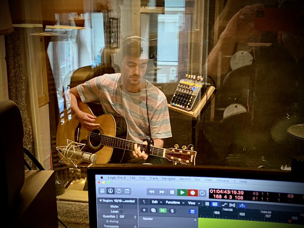 Matt Hall recording guitar in the booth